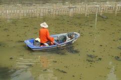 Les travailleurs d'hygiène nettoient les déchets en rivière Image libre de droits