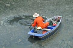 Les travailleurs d'hygiène nettoient les déchets en rivière Photos stock