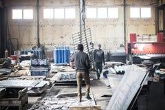 Les travailleurs dans les bottes marchent à l'intérieur de l'usine industrielle image libre de droits