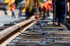 Les travailleurs dans des uniformes lumineux étendent les voies ferroviaires ou de tram photo libre de droits