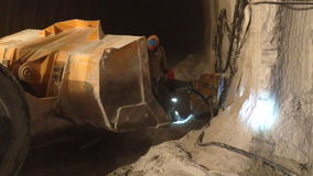 Les travailleurs dans l'uniforme et les casques travaillent dans le tunnel souterrain banque de vidéos