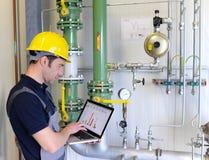 Les travailleurs dans un ensemble industriel vérifient les systèmes avec technique moderne photo stock