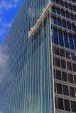 Les travailleurs de la construction sur l'oscillation présentent le travail haut sur le nouveau bâtiment Images stock