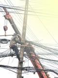 Les travailleurs de réparation balancent sur des courriers de câble pour fixer la ligne de dedans Photo libre de droits