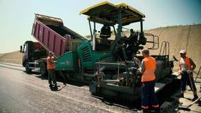 Les travailleurs de route étendent le nouvel asphalte sur la construction de routes banque de vidéos