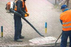 les travailleurs de service à la communauté nettoient le trottoir images stock