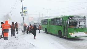 Les travailleurs de service collectif nettoient des trottoirs de neige et glacent près de la route avec les voitures mobiles banque de vidéos