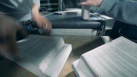 Les travailleurs emballent le papier imprimé, fin  banque de vidéos