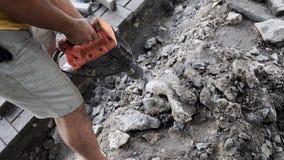 Les travailleurs emploient le briseur concret électrique Travailleur de sexe masculin réparant la surface d'allée avec le marteau clips vidéos