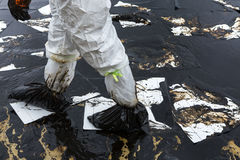 Les travailleurs enlèvent et nettoient le pétrole brut renversé avec le PAP absorbant image libre de droits