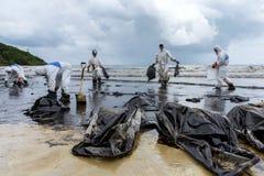 Les travailleurs enlèvent et nettoient le pétrole brut renversé avec le PAP absorbant image stock
