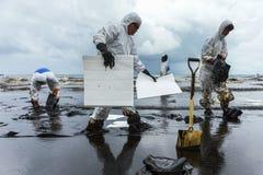 Les travailleurs enlèvent et nettoient le pétrole brut renversé avec le PAP absorbant photo libre de droits