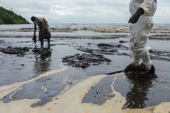 Les travailleurs enlèvent et nettoient le pétrole brut renversé avec le PAP absorbant photos stock
