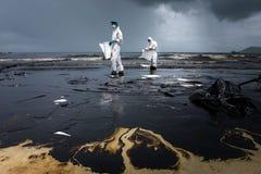 Les travailleurs enlèvent le pétrole brut d'une plage Photos stock