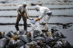 Les travailleurs enlèvent le pétrole brut d'une plage Photo stock