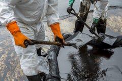 Les travailleurs enlèvent le pétrole brut d'une plage, pétrole brut sur la flaque d'huile photographie stock libre de droits