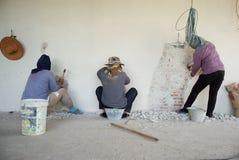 Les travailleurs enlevant le ciment plâtré apprêtent sur le maçon photographie stock libre de droits