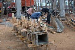 Les travailleurs fait la colonne enfermer dans une boîte et garder par la grue pour la colonne construite Photo stock
