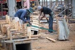 Les travailleurs fait la colonne enfermer dans une boîte et garder par la grue pour la colonne construite Photographie stock libre de droits