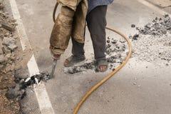 Les travailleurs forent la route dans la conduite d'eau après la coordination avec le département de route photo stock
