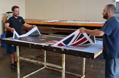 Les travailleurs impriment le drapeau national du Nouvelle-Zélande Image libre de droits