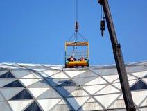 Les travailleurs inspectent le toit d'un grand bâtiment Image stock