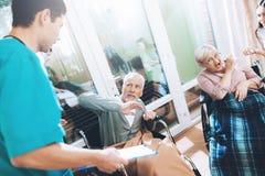 Les travailleurs médicaux discutent avec un couple plus âgé dans une maison de repos Images libres de droits