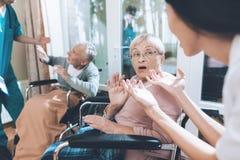 Les travailleurs médicaux discutent avec un couple plus âgé dans une maison de repos Photographie stock