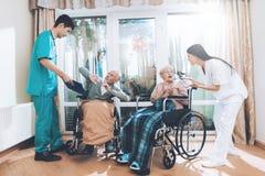Les travailleurs médicaux discutent avec un couple plus âgé dans une maison de repos Image libre de droits