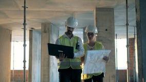 Les travailleurs marchent dans un bâtiment, regardant un ordinateur portable, fin  clips vidéos