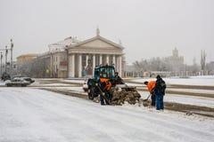Les travailleurs nettoient la neige dans la place Photographie stock