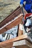 Les travailleurs ont coupé les combles sur le toit de la maison de tronçonneuse photographie stock libre de droits