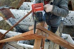 Les travailleurs ont coupé les combles sur le toit de la maison de tronçonneuse photo libre de droits