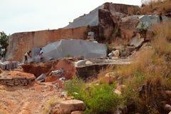 Les travailleurs ont séparé le morceau énorme de roche schisteuse et font à partir de lui la pierre de place Image libre de droits