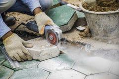 Les travailleurs pave des planchers de brique photo stock
