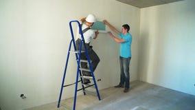 Les travailleurs pour deux hommes au chantier de construction colle le papier peint au mur banque de vidéos