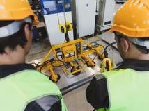 Les travailleurs s'approchent du dispositif de levage de feuillard Photo stock