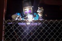 Les travailleurs soudent la maille en acier dans la zone de manoeuvre Images stock