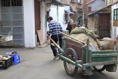 Les travailleurs tirent la charette à bras en bois Photos stock