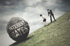 Les travailleurs tirent une pierre avec le texte de taux d'intérêt Images libres de droits