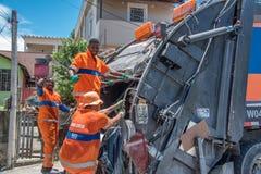 Les travailleurs urbains du COMLURB municipal mettant des déchets dans réutiliser le camion à ordures photos stock