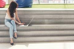 Les travailleuses actives utilisent l'ordinateur portable d'ordinateur se reposant sur l'escalier Images libres de droits