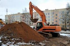 Les travaux de construction de réparation, l'excavatrice hydraulique sur la chenille au cours de couleur orange, un grand tas de  images libres de droits