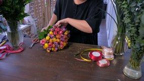 Les travaux de femme de fleuriste fait le bouquet à partir des roses colorées dans le magasin, plan rapproché de mains clips vidéos