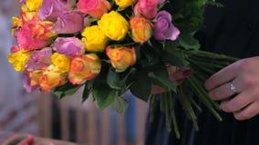 Les travaux de femme de fleuriste fait le bouquet à partir des roses colorées dans le magasin, vue de plan rapproché banque de vidéos