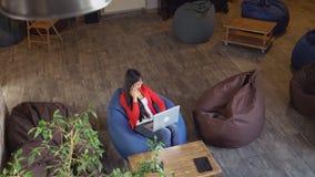 Les travaux des femmes attrayants avec l'ordinateur portable a la conversation d'affaires banque de vidéos