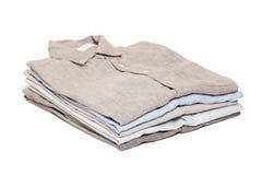 Les travaux domestiques repassants repassés ont plié le fond blanc propre de chemises Image libre de droits