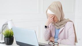 Les travaux et les types musulmans fatigu?s de femme sur l'ordinateur portable, met ses verres et frotte ses yeux banque de vidéos