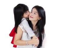 Les étreintes d'enfant et embrassent sa mère Image stock