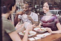 Les trois amis joyeux prennent le déjeuner Photographie stock